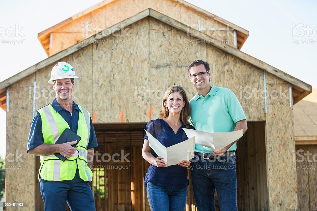 Builder and couple at new home under construction stock photo