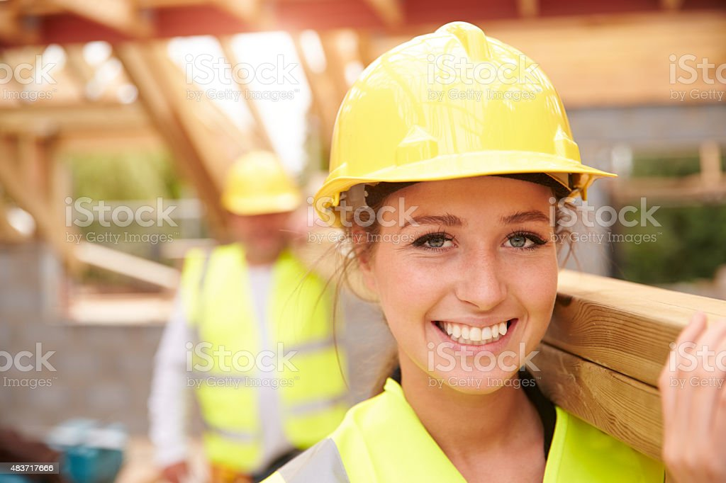 Builder And Female Apprentice Carrying Wood On Site stock photo