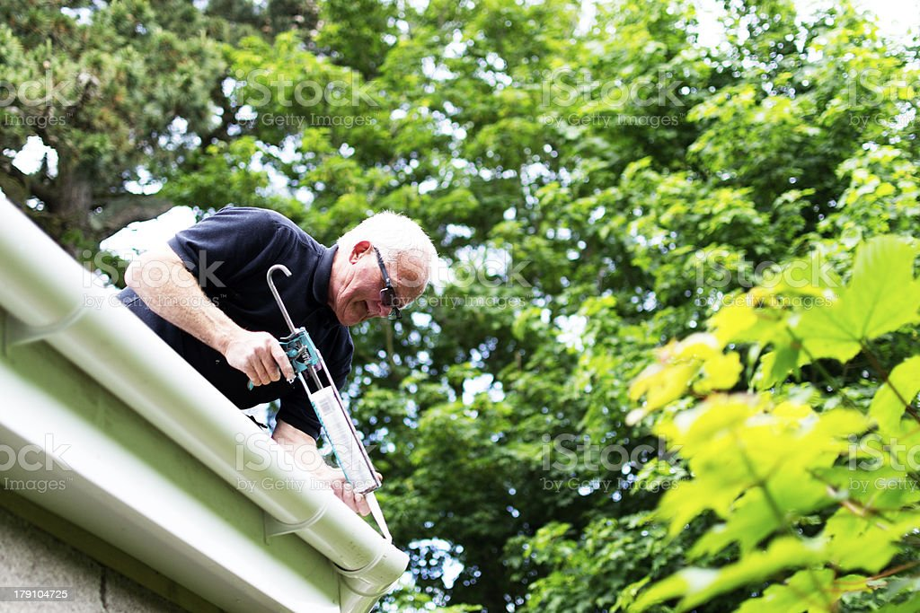 Builder applying seal to guttering stock photo