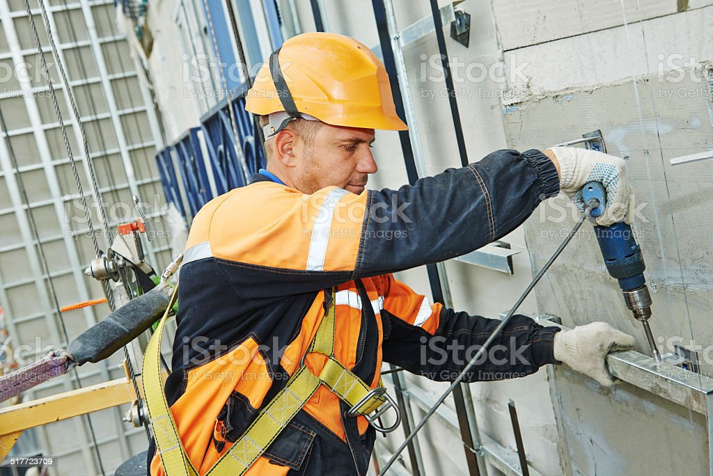 builder at facade construction work stock photo