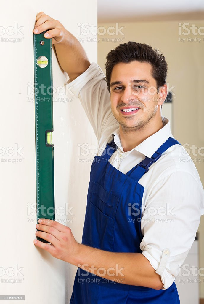 Builder checking floor with level stock photo