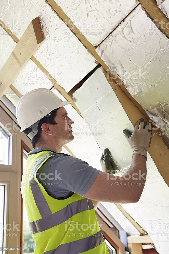 Builder Fitting Insulation Boards Into Roof Of New Home stock photo