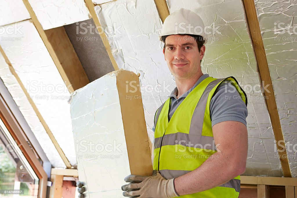 Builder Fitting Insulation Boards Into Roof Of New House stock photo