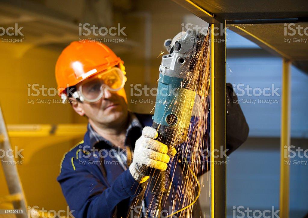 Builder grinding welds on metallic construction stock photo