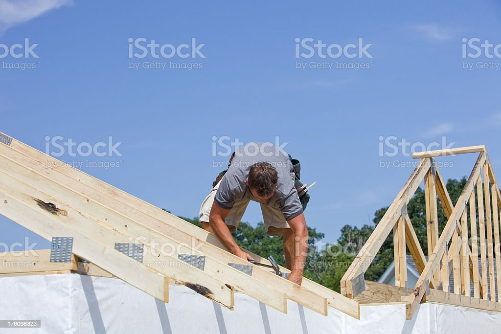 Builder Hammering Roof Truss Nail Against Blue Sky royalty-free stock photo