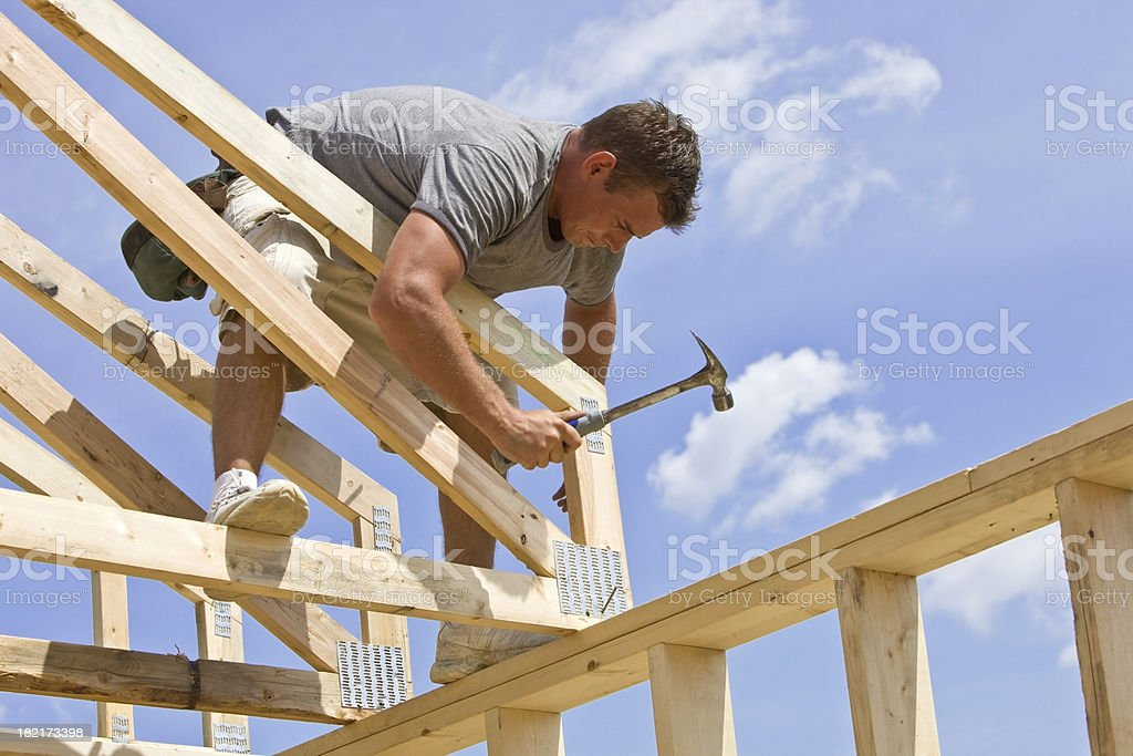 Builder Hammering Roof Truss Nail Against Blue Sky stock photo