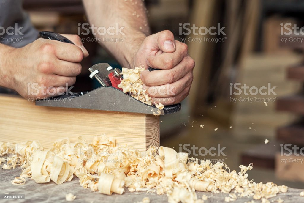 builder handles a wooden plank board jack plane stock photo