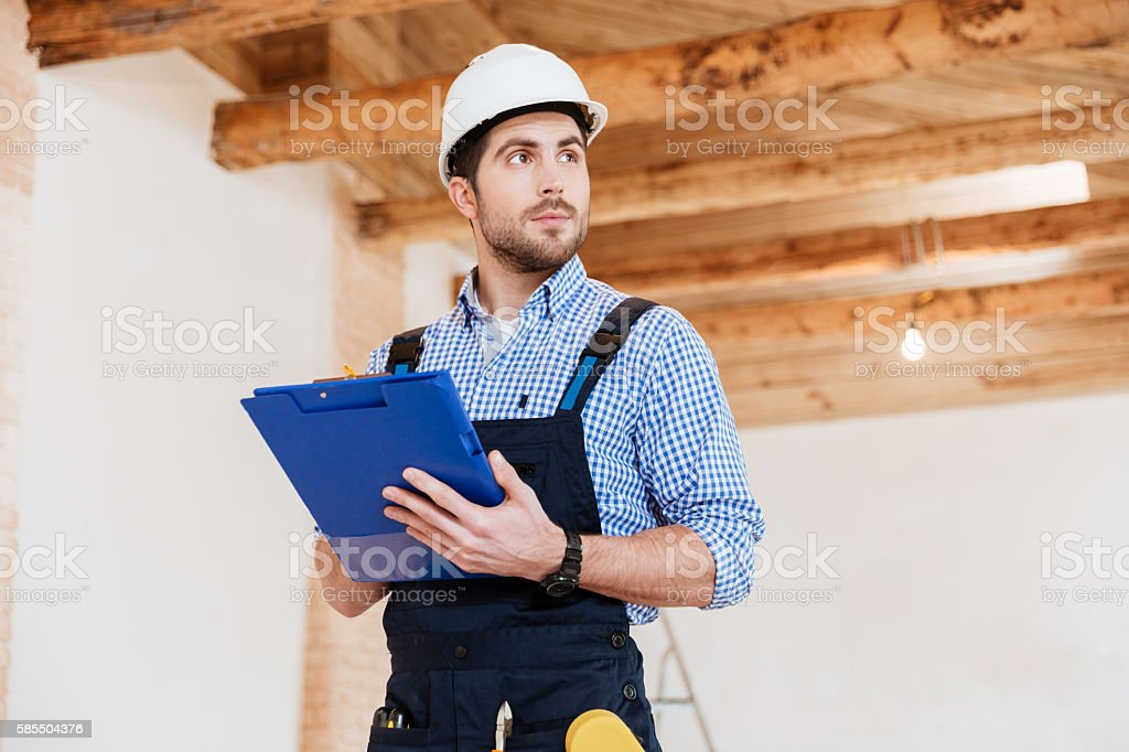 Builder in hardhat with clipboard and pencil indoors stock photo