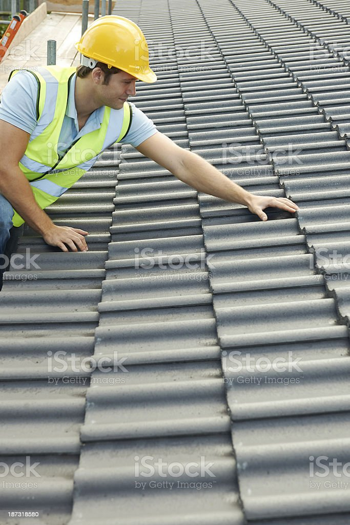 Builder inspecting the roof of new building on a cloudy day royalty-free stock photo