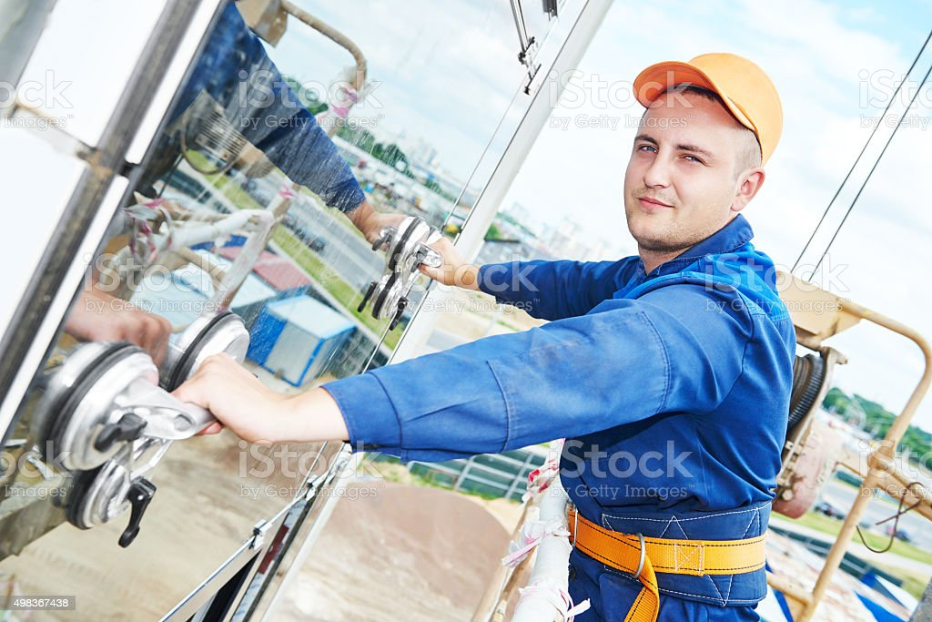 builder installing glass windows on facade stock photo