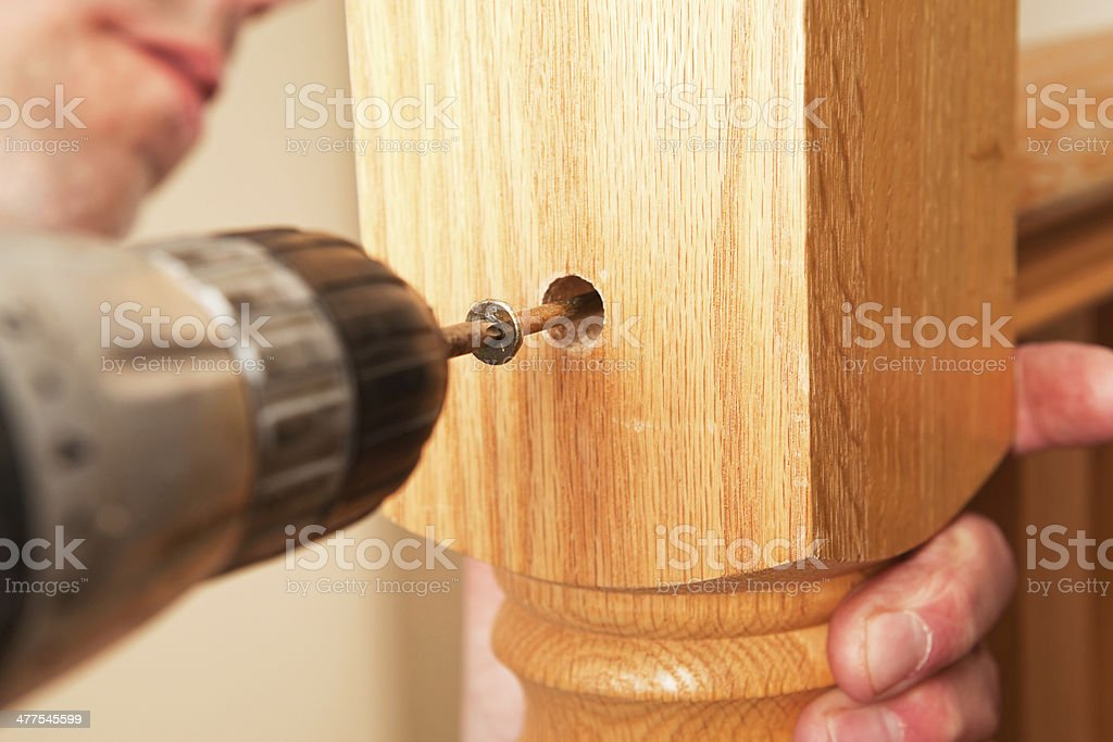 Builder Installing Stair Railing Newel Post with Torx Screw stock photo