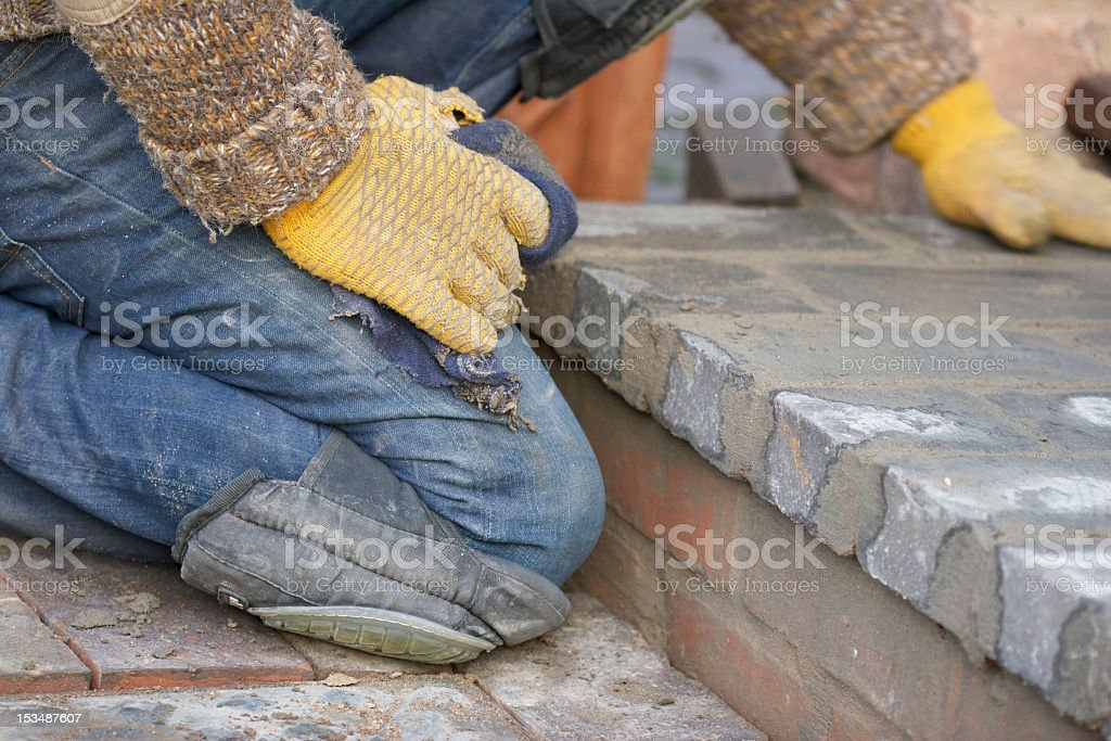 Builder Laying Blue Paving Bricks stock photo