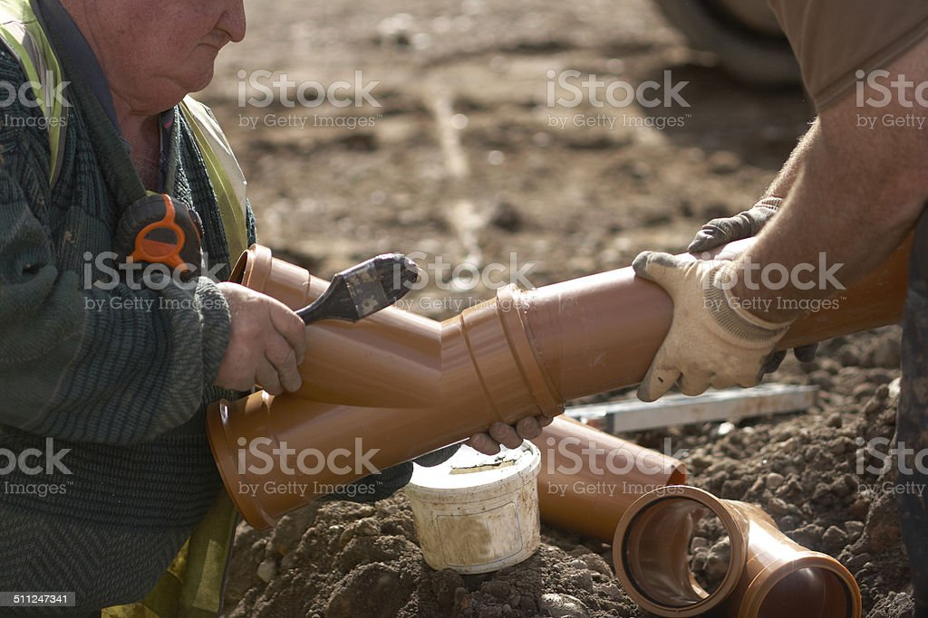 Builder Laying Sewage Pipe On Site 1 stock photo