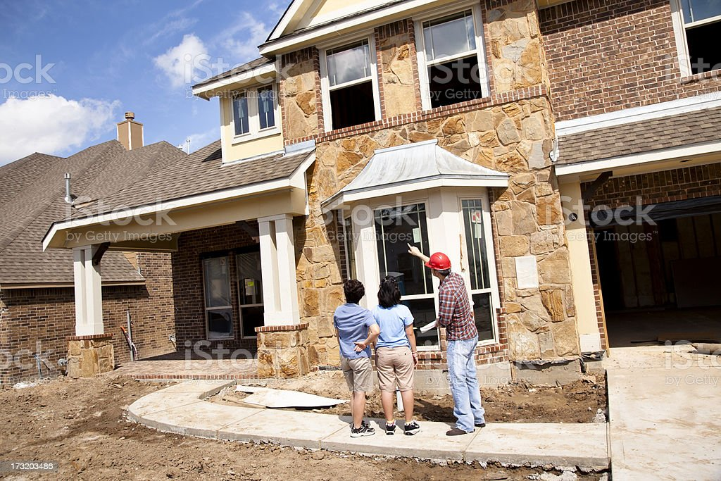Builder meeting with woman and daughter at new home construction royalty-free stock photo