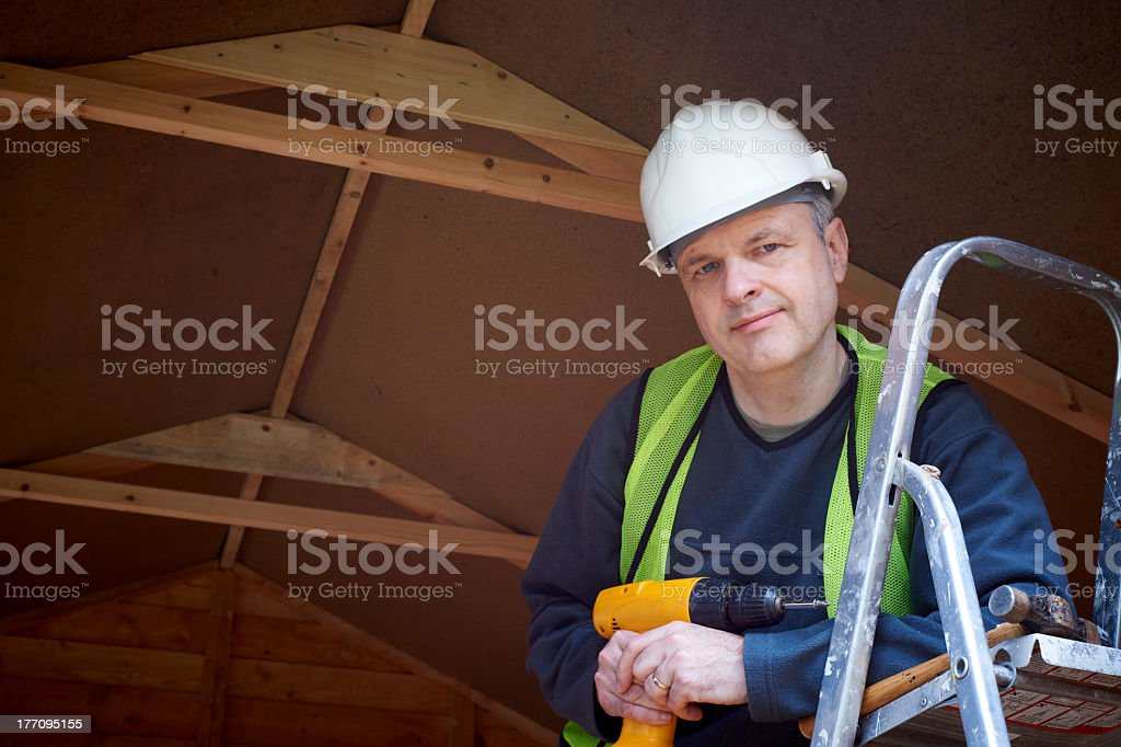 Builder on a ladder holding electric drill royalty-free stock photo