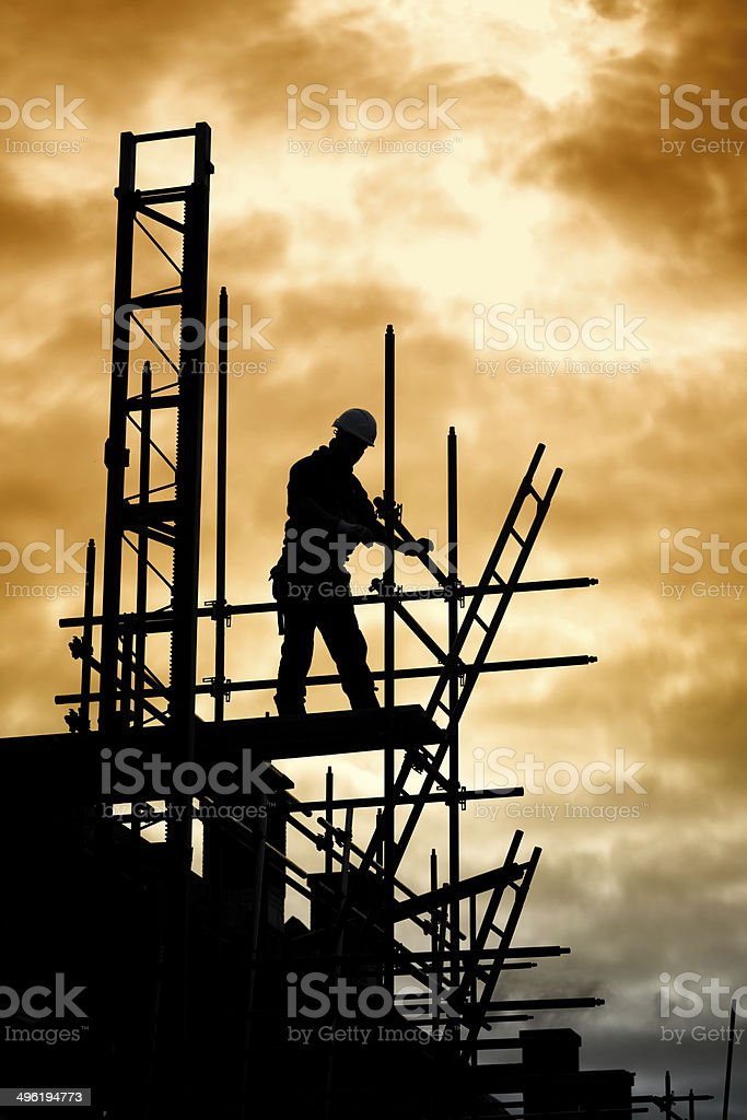 builder on scaffold building site stock photo