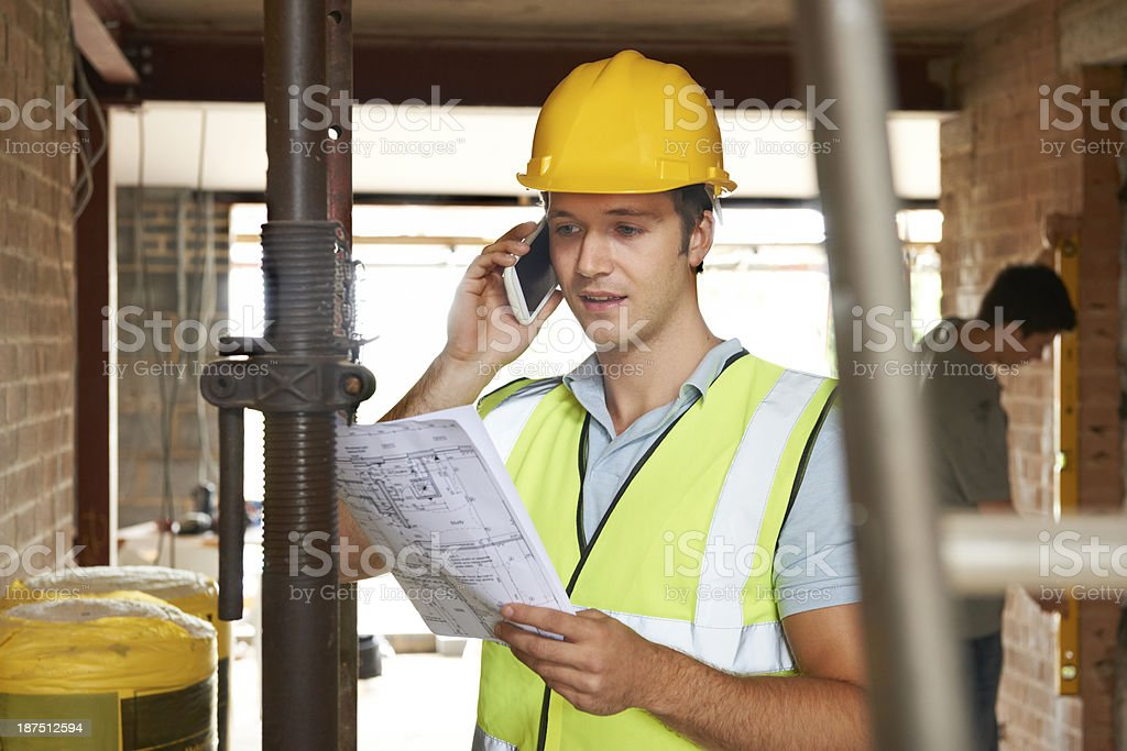 Builder On Site Using Mobile Phone stock photo