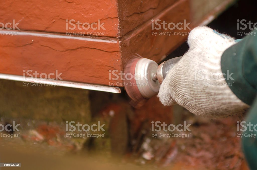 Builder polishing the red wall. House environment theme stock photo