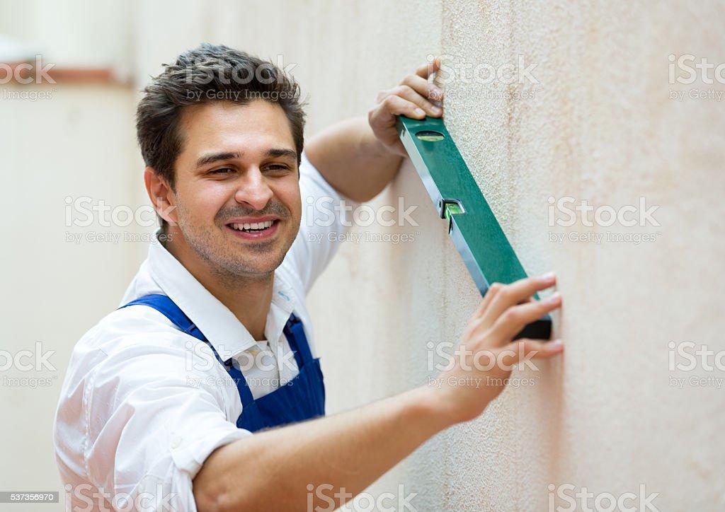 builder posing with spirit level stock photo
