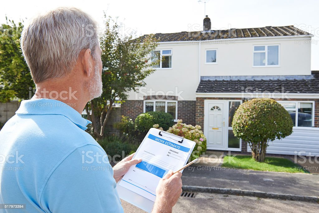 Builder Preparing Estimate For Exterior Home Improvement stock photo