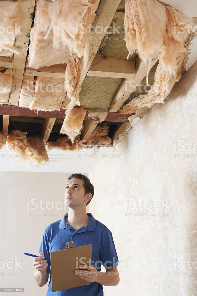 Builder Preparing Quote For Damage To Ceiling stock photo
