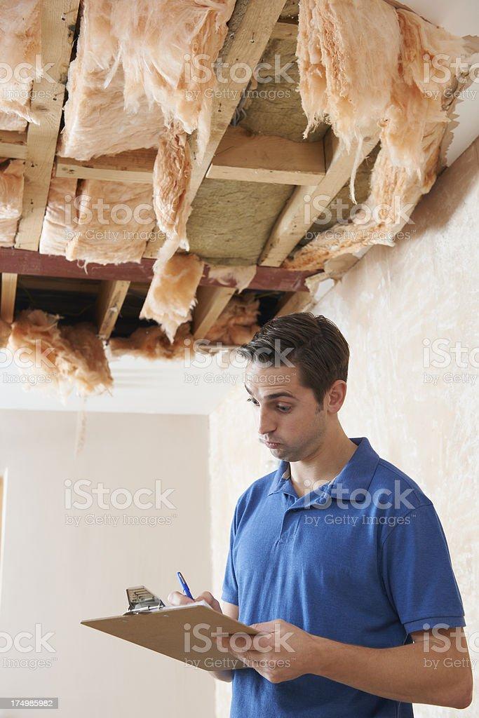 Builder Preparing Quote For Repair To Ceiling stock photo