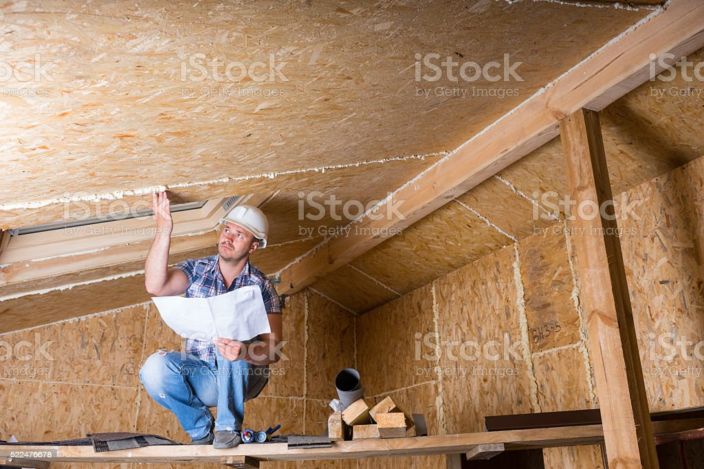 Builder Reading Plans Inside Unfinished Home stock photo