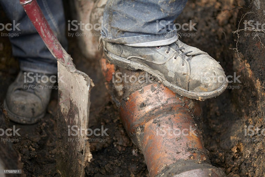 Builder Repairing Sewerage Pipe On Site stock photo