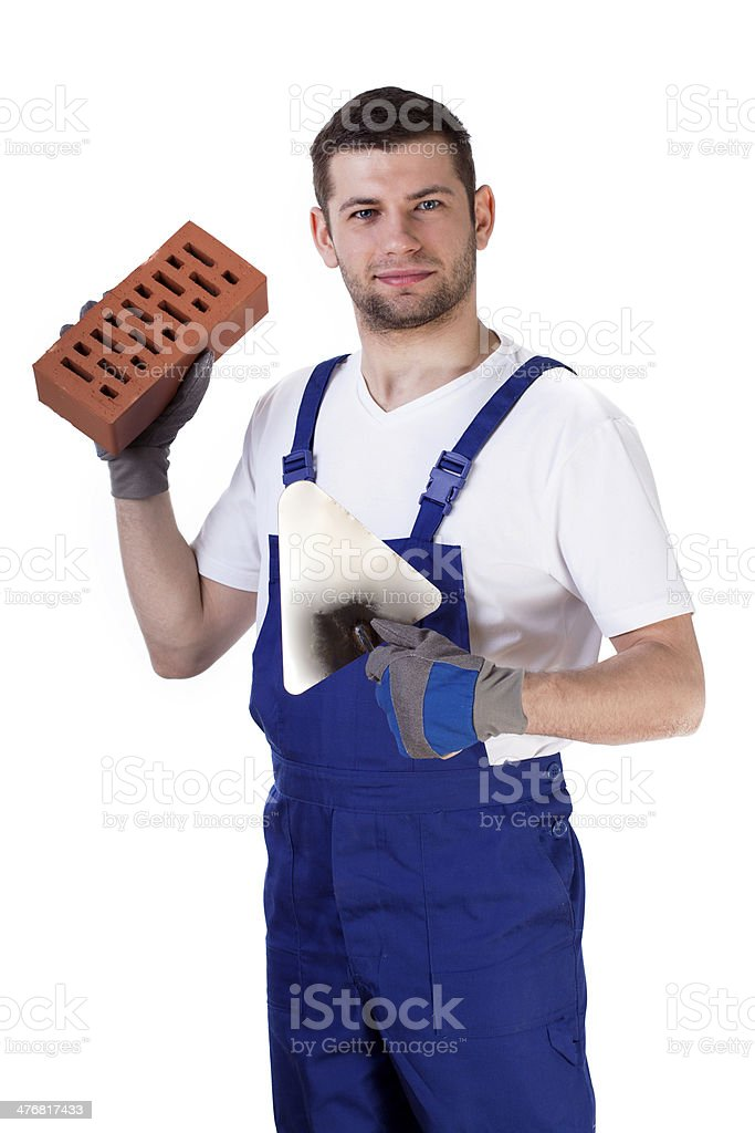 Builder standing with brick and spatula royalty-free stock photo
