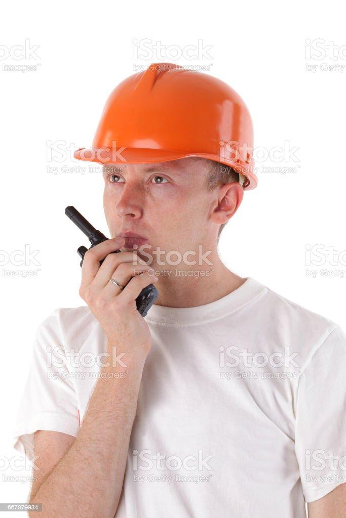 builder talking on portable UHF radio transceiver isolated on white stock photo
