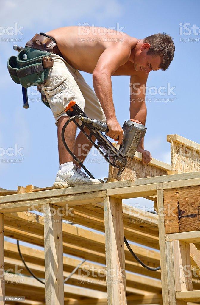 Builder Using Air Nail Gun to Secure Floor Truss Joist stock photo