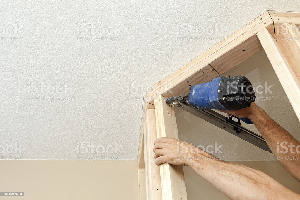 Builder Using Air Nailer to Fasten Wall Stud stock photo