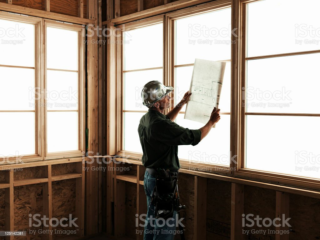 Builder with Blueprints in Front of Window stock photo