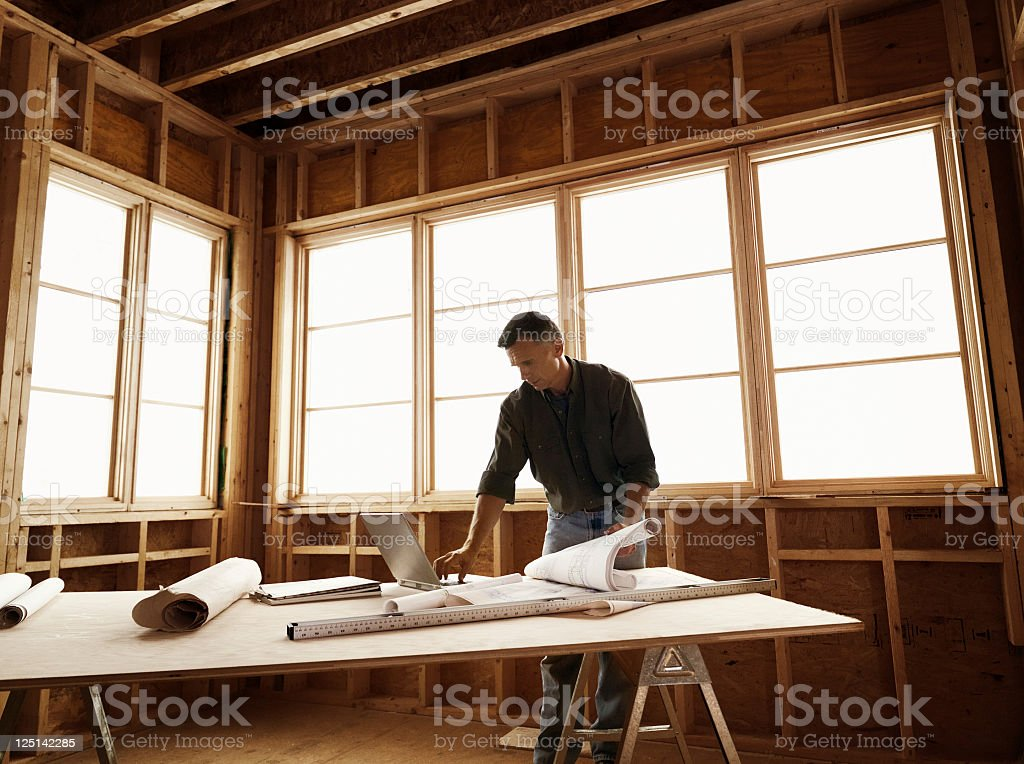 Builder with Blueprints on Plywood Table stock photo