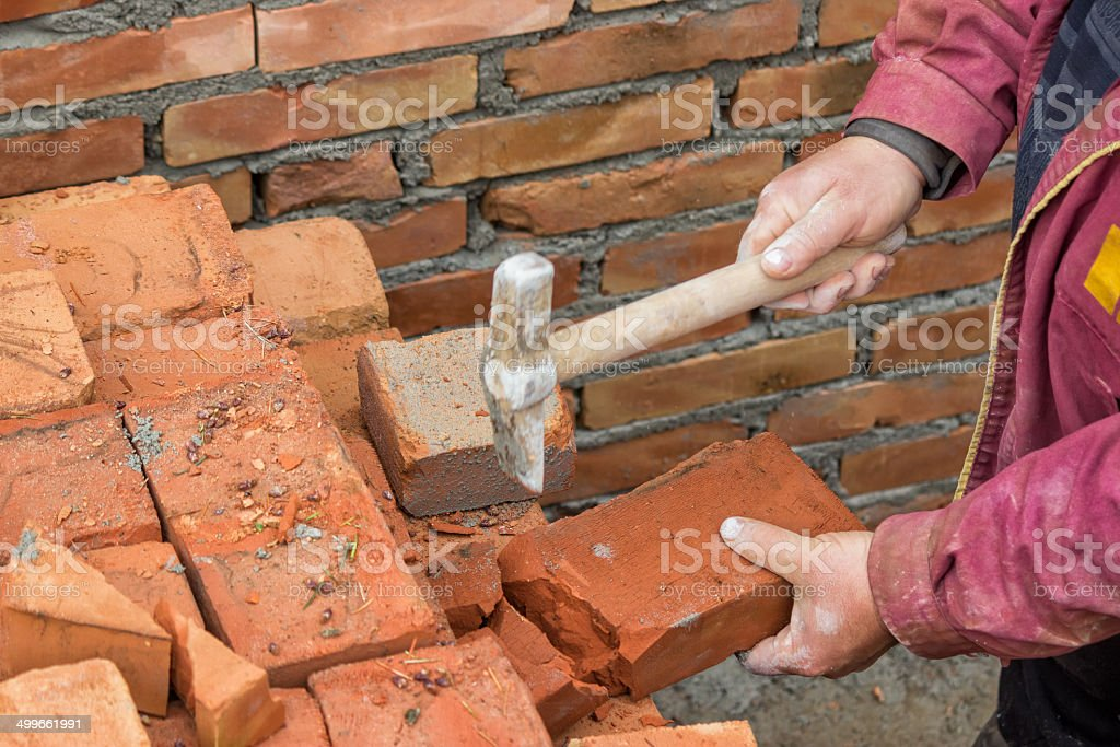 Builder worker cutting a brick 2 stock photo