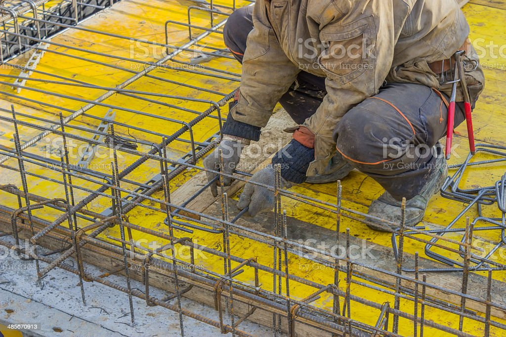 Builder worker gearing up steel rods for a concrete stock photo