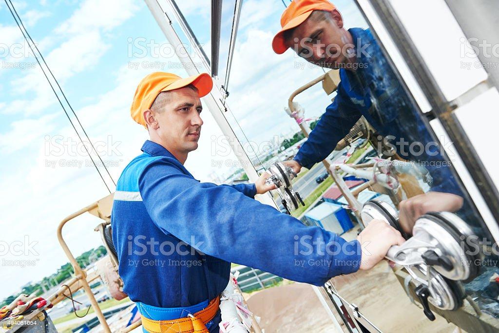 builder worker installing glass windows on facade stock photo