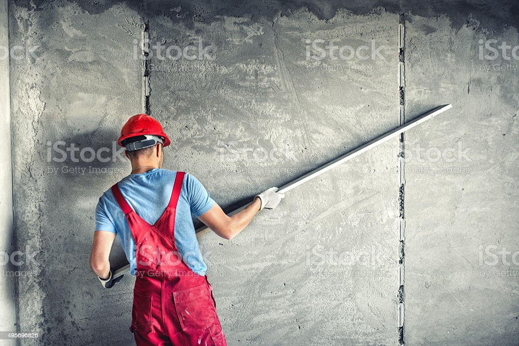 builder worker plastering facade industrial building with leveler stock photo
