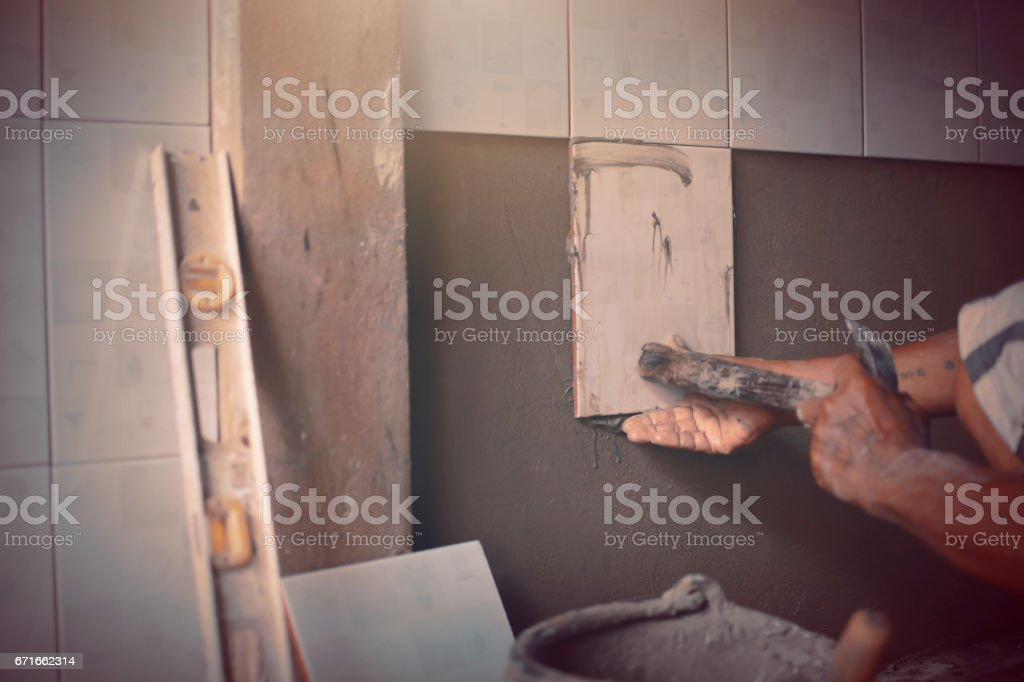 Builder worker renovate the wall lay out textiles. stock photo