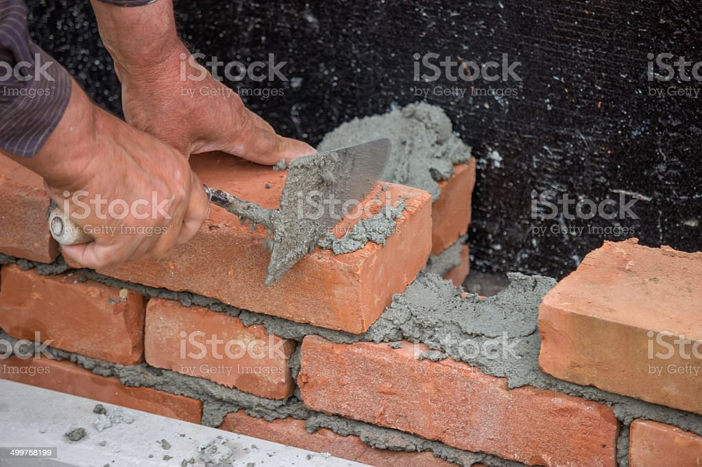 Builder worker with trowel building brick wall stock photo