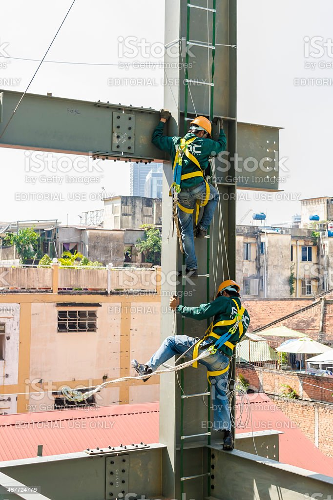 Builder workers in safety protective assemble metal construction frame stock photo