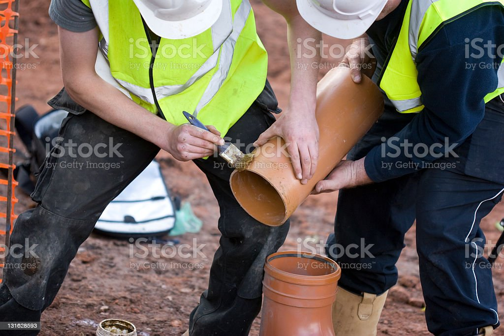 Builders fitting together a sewage pipe on a building site stock photo