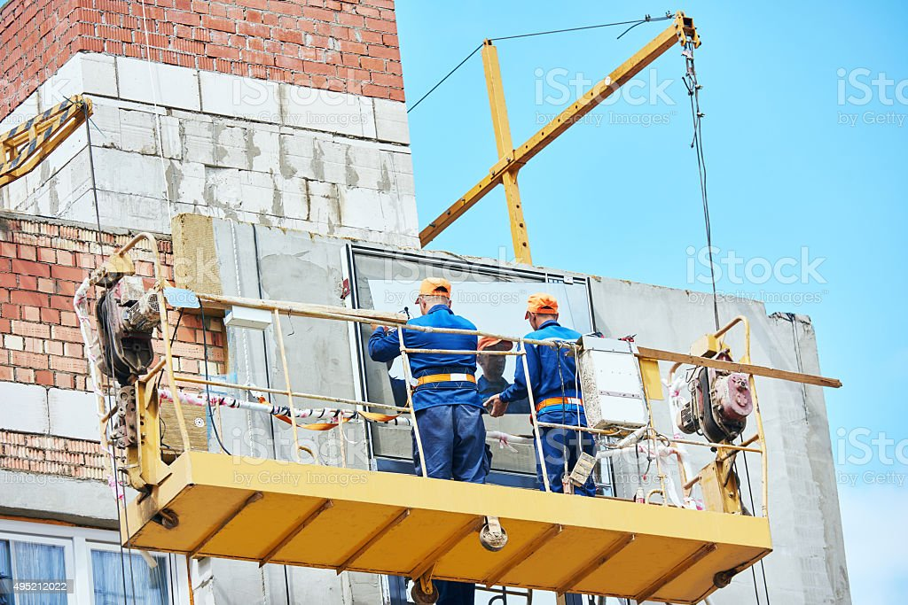builders worker installing glass windows on facade stock photo
