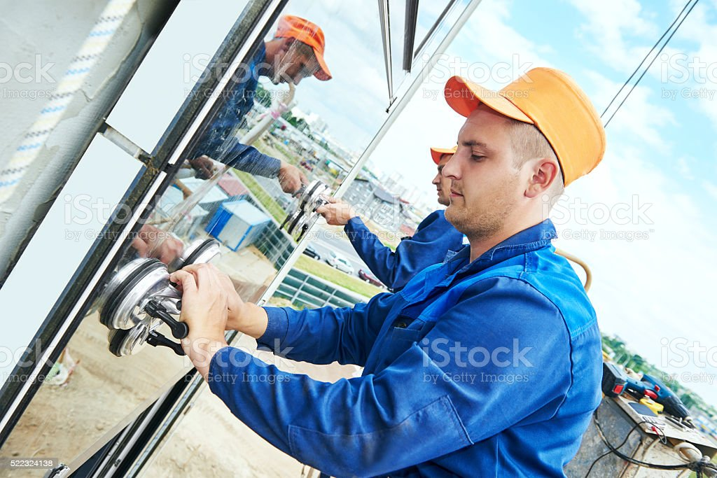 builders worker installing glass windows on facade stock photo