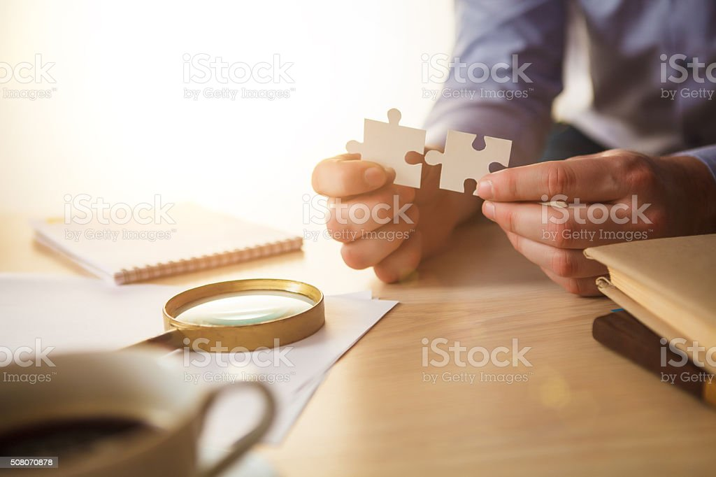 Building a business success. The hands with puzzles stock photo