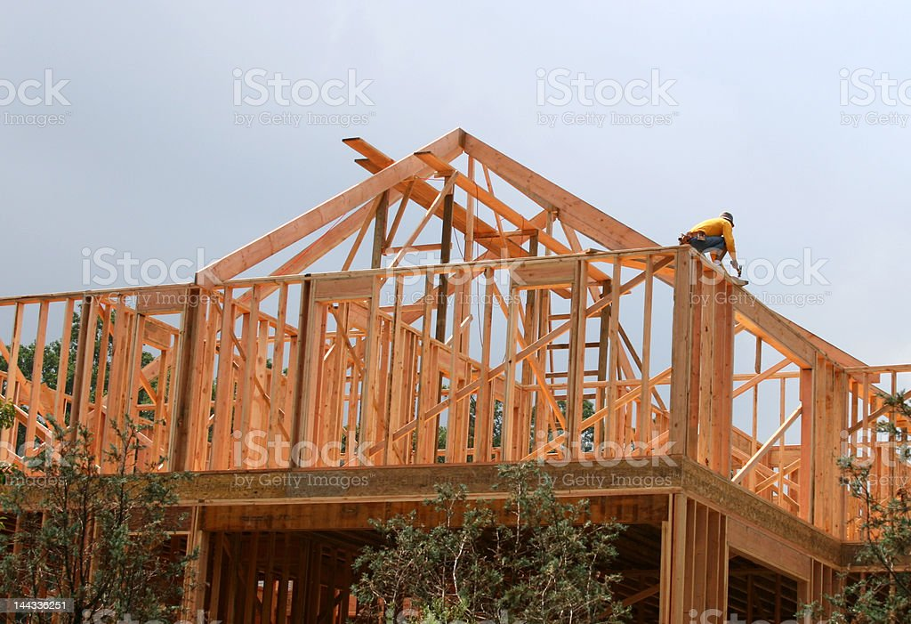 Building a new home (roof work by one worder) royalty-free stock photo