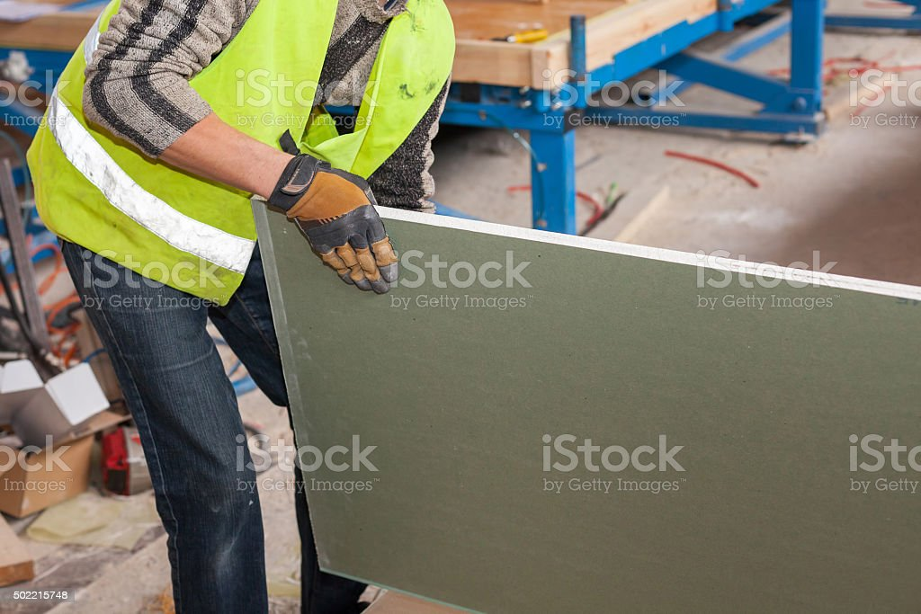 Building a wall for frame house. Worker holding a drywall stock photo