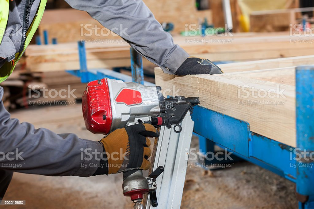 Building a wall for frame house.Worker use Framing Nailer stock photo