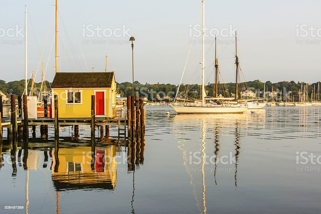 Building and large sailboats in early sunlight stock photo