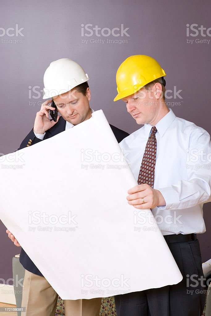 Building Architects Reviewing Blueprints royalty-free stock photo